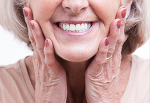 Elderly woman with gray hair smiling with dentures from Palo Alto Oral Health